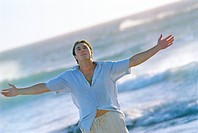 Serious man with arms outstretched standing on beach