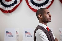 Hispanic voter standing in polling place (thumbnail)