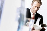 Serious businessman reviewing report in office