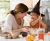 Caucasian mother and witch daughter baking together