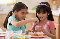 Girls decorating cupcakes together