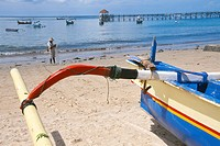 Asia, Indonesia, Bali, Jimbaran fishing village. Colorful jukungs outriggers with Balinese fisherman in the background.