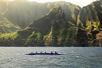 Crew paddling canoe in ocean