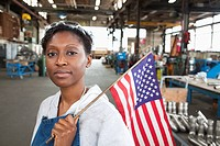 Black worker standing in factory with American flag