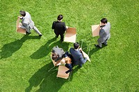 Business people carrying chairs outdoors