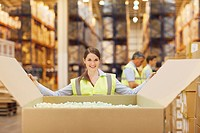 Woman in warehouse closing cardboard box
