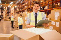 Worker with laptop checking box in warehouse