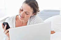 Woman with laptop text messaging on cell phone