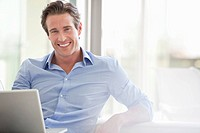 Smiling man sitting with laptop