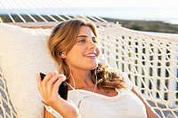 Woman laying in hammock listening to mp3 player