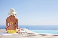 Woman in bikini sitting near swimming pool (thumbnail)