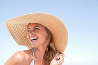 Smiling woman in sun hat outdoors