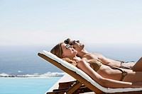 Couple laying in lounge chairs sunbathing together