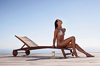 Teenager in bikini sitting on lounge chair