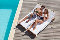Couple laying on lounge chairs reading books near swimming pool