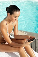 Teenager in bikini text messaging on cell phone near swimming pool