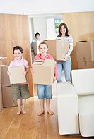Family carrying moving boxes into new home