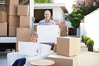 Couple holding blank cards near boxes and moving van