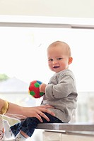 Smiling baby holding ball (thumbnail)