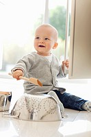 Baby banging on colander with wooden spoon