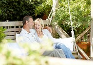 Couple sitting on backyard swing together