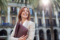 Businesswoman holding briefcase outdoors