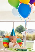 Baby in high chair with birthday cake and balloons