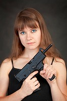 Serious beauty armed with submachine gun on a black