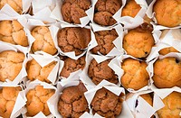 lots of freshly baked small muffins cakes in rows