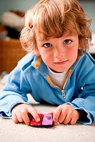 Young boy playing at home with two toy cars (thumbnail)