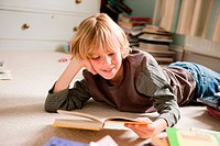 Young boy lying on his front, reading a book in his bedroom