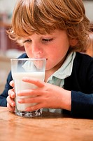 Young boy drinking a large glass of milk