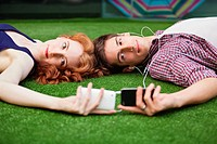 Couple lying down looking at mobile phones