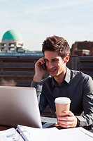 Man using laptop and mobile phone whilst having coffee on a rooftop