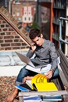 Young man working with a laptop on a rooftop