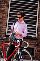 Man holding digital tablet behind a bike