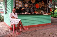 Local shopkeeper at his wooden cabin selling tourist souvenirs, Victoria, Mahe Island, Seychelles