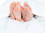 Close_up of the feet of a couple on the bed