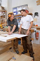 Germany, Upper Bavaria, Schaeftlarn, Carpenters preparing blue print