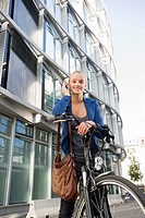 Germany, Bavaria, Teenage girl with cell phone on bicycle, smiling