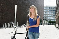 Germany, Cologne, Young woman with bicycle, smiling