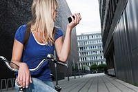 Germany, Cologne, Young woman with cell phone