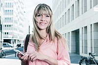 Germany, Cologne, Young woman with cell phone, smiling, portrait