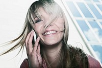 Germany, Cologne, Young woman using cell phone, smiling, portrait