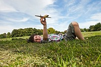 Germany, Bavaria, Boy playing with model airplane in park, smiling, portrait