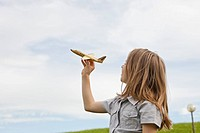 Germany, Bavaria, Girl playing with model airplane in park