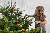 Germany, Munich, Girl decorating christmas tree