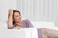 Germany, Munich, Woman sitting on couch, smiling