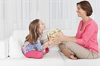 Germany, Munich, Mother and daughter with gift, smiling