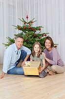 Germany, Munich, Family sitting by christmas tree with gift, smiling, portrait